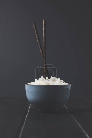 bowl of freshly cooked rice with chopsticks on black table