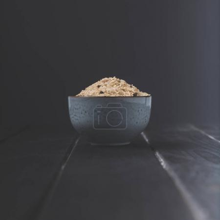 bowl of raw rice with spices on black table