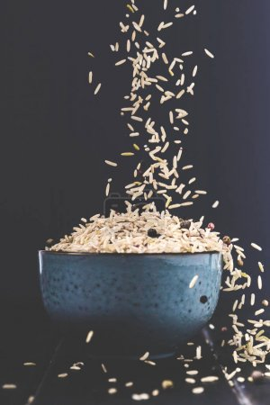 Photo for Close-up shot of rice spilling into bowl on black table - Royalty Free Image