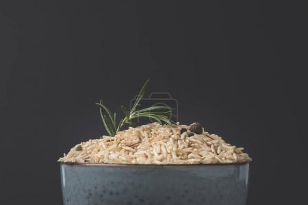close-up shot of bowl of raw rice with rosemary and spices on black surface