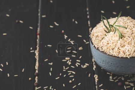 Photo pour Bol de riz cru avec romarin sur surface noire - image libre de droit