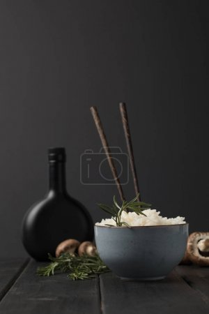 Photo for Bowl of tasty rice with mushrooms and bottle of soy sauceon black tabletop - Royalty Free Image