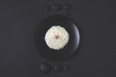 top view of tasty rice on plate with pebbles on black table