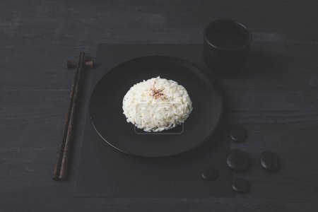 rice with cup of tea and chopsticks on black table