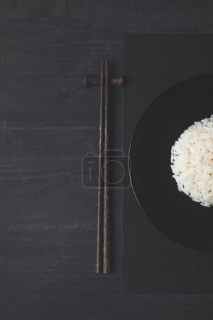 Photo pour Vue de dessus du riz et baguettes sur tableau noir - image libre de droit