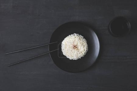 top view of rice on plate with chopsticks on black table