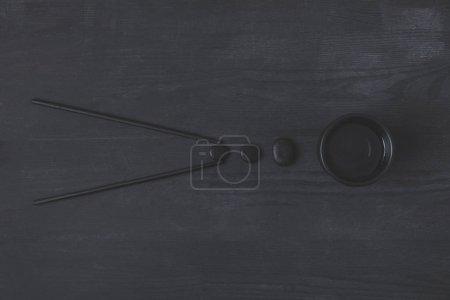 Photo pour Composition créative des baguettes avec tasse de thé chinois et des cailloux sur fond noir - image libre de droit