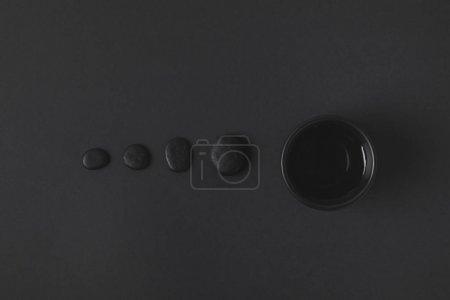 Photo pour Vue de dessus de la tasse de thé chinois et galets sur la surface noire - image libre de droit