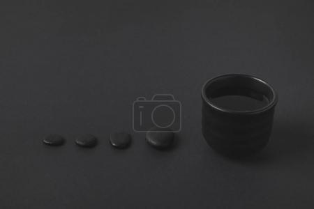 Photo pour Tasse à thé chinois et galets sur la surface noire - image libre de droit