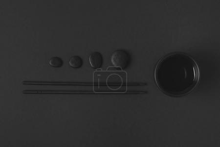 top view of chopstick with chinese tea cup and pebbles on black