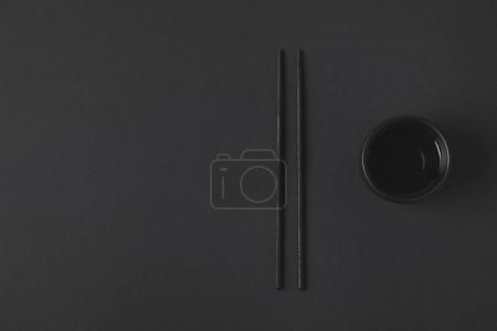 top view of chopstick with chinese tea cup on black