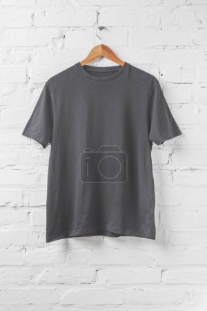 Photo for One dark grey shirt on hanger on white wall - Royalty Free Image