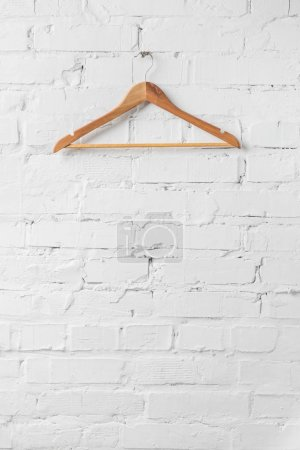 Photo for One brown wooden hanger on white wall - Royalty Free Image