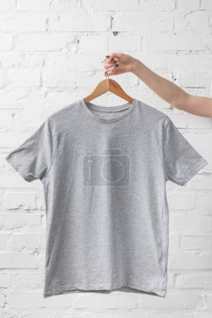 Photo for Cropped image of woman holding grey shirt on hanger - Royalty Free Image