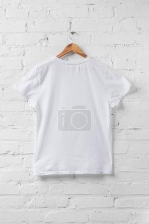 Photo for One white shirt on hanger on white wall - Royalty Free Image