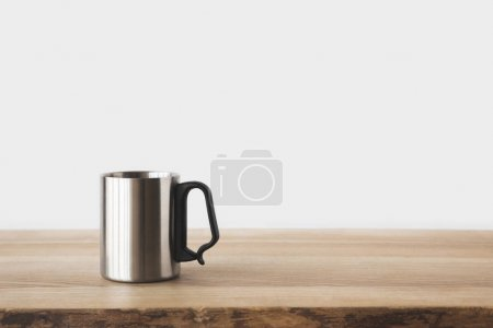 one silver cup on wooden table on white