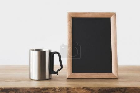 silver cup and blackboard in frame on wooden table on white