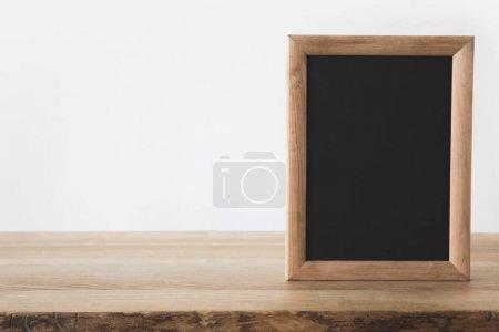 one empty blackboard on wooden table on white