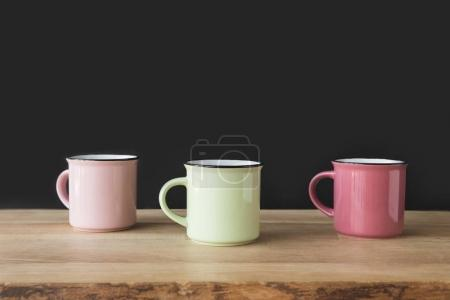 three colored cups on wooden table on black