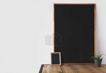 different blackboards and potted plant on wooden table on white