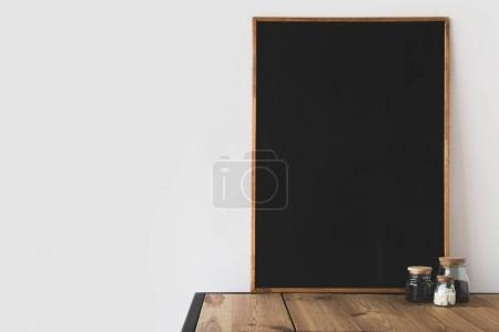 glass bottles with coffee beans and refined sugar and blackboard on wooden table