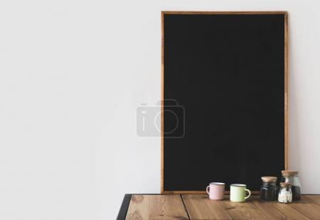 cups and coffee with big empty blackboard on wooden table on white