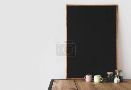 Photo pour Tasses et café avec grand tableau noir vide sur table en bois sur blanc - image libre de droit
