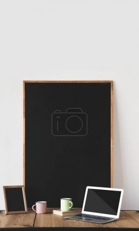 empty blackboards in frames with cups and laptop on table on white
