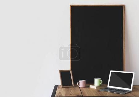 empty blackboards in frames with cups and laptop on white