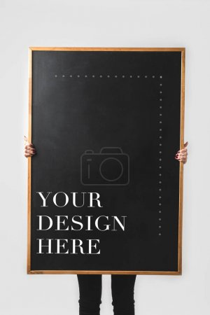 woman holding big black board with text your design here isolated on white