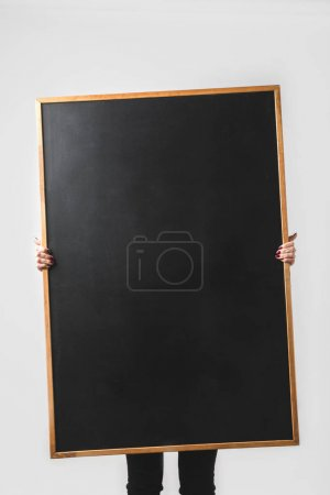 woman holding big empty black board isolated on white
