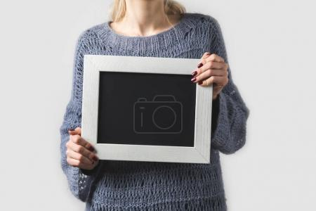 cropped image of woman holding empty black board isolated on white