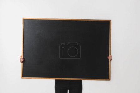 Photo for Woman holding big empty black board isolated on white - Royalty Free Image