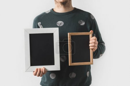 cropped image of man holding empty black boards isolated on white