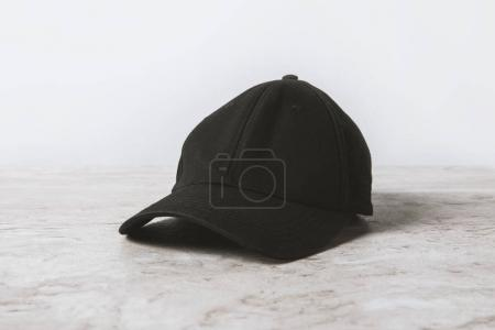 one black cap on wooden table on white