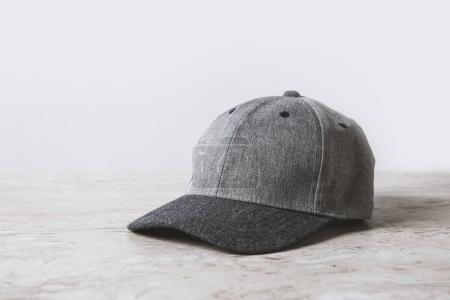 one grey cap on wooden table on white