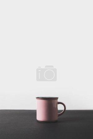 Photo pour Une tasse rose sur table noire sur blanc - image libre de droit