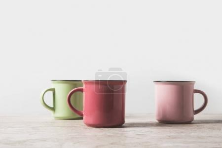 three colored cups on marble table on white