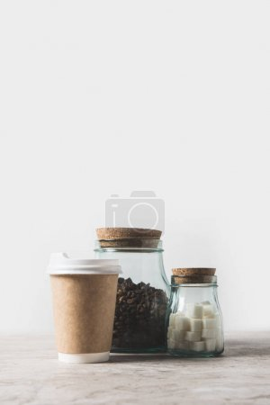 Photo for Coffee beans, refined sugar and disposable coffee cup on marble table on white - Royalty Free Image