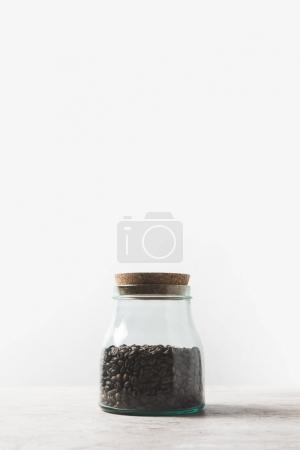 coffee beans in glass bottle on marble table on white