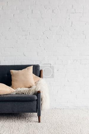 Photo for Cropped shot of couch with pillows and blanket in living room with white brick wall, mockup concept - Royalty Free Image