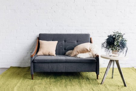Photo for Comfy couch in modern living room with white brick wall and flower pot on table, mockup concept - Royalty Free Image