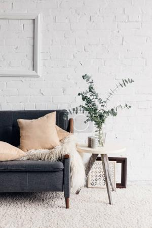 modern living room interior with cozy couch and flower in pot on table, mockup concept