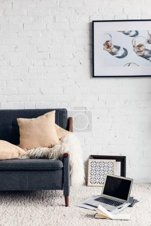 partial view of modern living room interior with cozy couch and picture on white brick wall, mockup concept