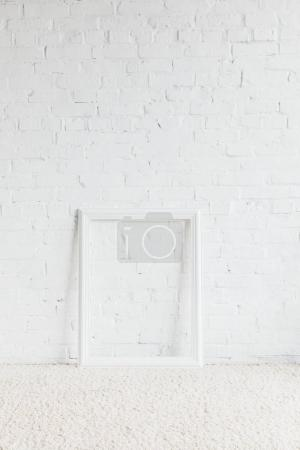 empty frame in front of white brick wall, mockup concept