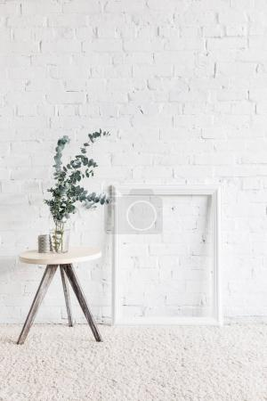 empty frame in front of white brick wall with flower pot on table, mockup concept