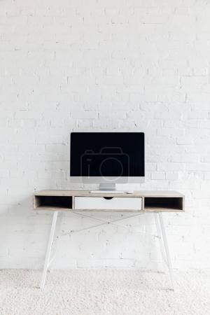 blank copmuter screen on empty workplace in front of white brick wall, mockup concept