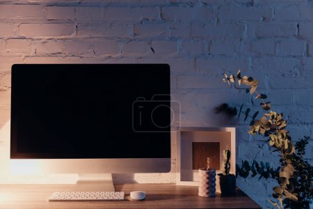 blank copmuter screen on workplace illuminated by table lamp in evening, mockup concept