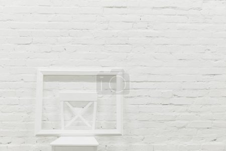 white brick wall with empty frame on chair, mockup concept