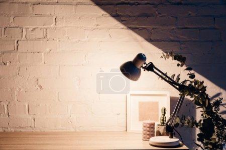 Photo pour Lampe de table illuminant mur de briques blanches vides, concept de maquette - image libre de droit